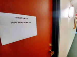 """office door with sign reading """"DO NOT ENTER ZOOM TRIAL GOING ON"""""""